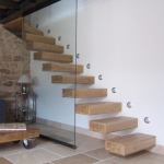 escalier suspendu bois clair accolé mur